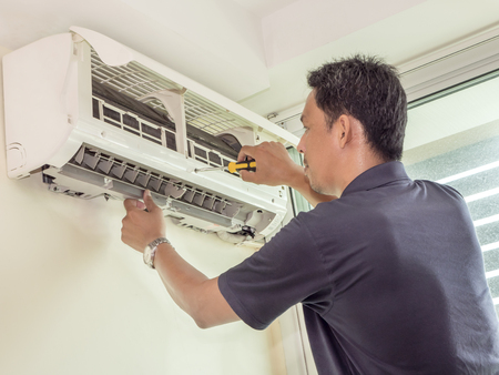 Single electrician man clean, fix and maintain air conditioning in the house 版權商用圖片