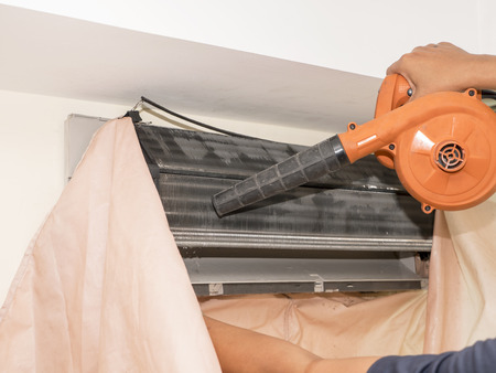 Single electrician man clean, fix and maintain air conditioning in the house Stock Photo
