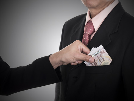 venal: Businessman giving a bribe  money to the pocket for corruption something in dark tone with clipping path