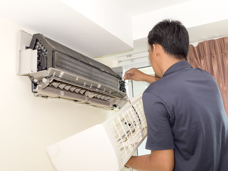 maintain: Single electrician man clean, fix and maintain air conditioning in the house Stock Photo