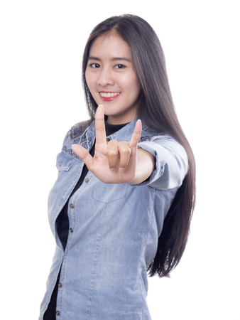 part of me: Woman in Jean shirt stand on isolated  white background smile and show hand sign I love you Foto de archivo