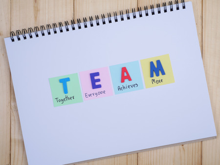 everyone: Word spelling TEAM and handwriting together, everyone, achieve, more on notebook with wood background (Business Concept)
