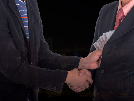 venal: Double exposure of businessman giving a bribe to the pocket with cityscape night light background. Corruption and fraud concepts Stock Photo