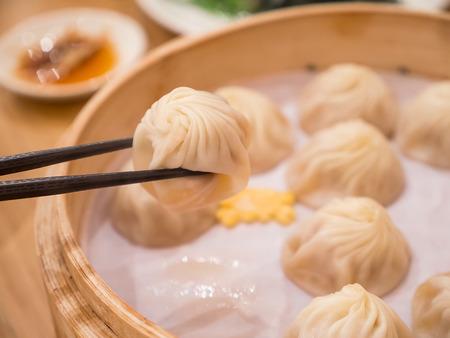 クローズ アップの小龍包、お箸でストリーミング豚肉餃子台湾食品 (選択と集中) 写真素材