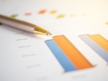 capital gains: Close pen on business charts and  graph with light effect (Selective focus)