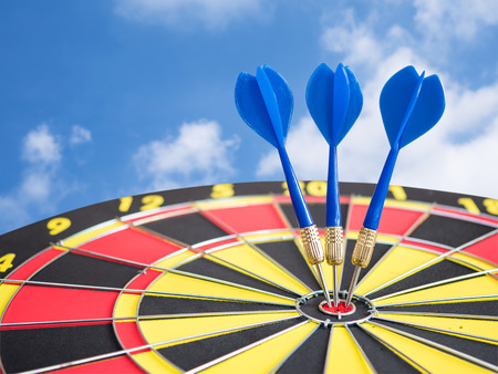 Dart arrows pin in the center of dart board with blue sky background (Business Concept)