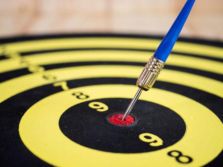 specific: Single dart arrow pin in the center of dart board. (Selective focus)
