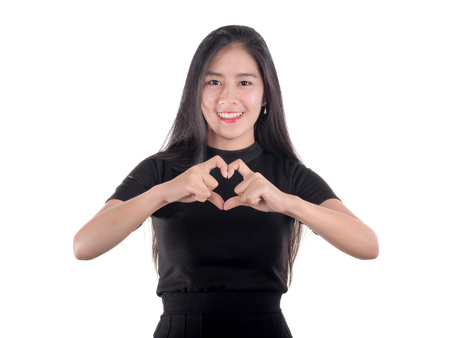 part of me: Woman in black shirt stand on isolated  white background smile and show hand sign with heart shape