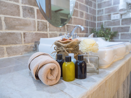 Liquid soap / shampoo bottle and brown towel on wash bowl in bathroom at the modern hotel (Selective Focus) Stock fotó