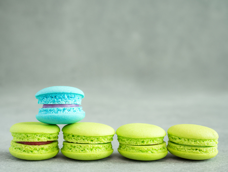 Blue color macaroon stand over assortment of green macaroon with copy space on cement or concrete wall background Stock fotó