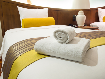 Two white laundered fluffy towels on white bed in bedroom interior at the hotel Stock Photo