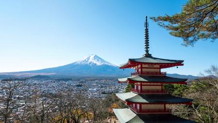 Landscape of Fuji mountain and red Pagoda with red leaf and dry tree under blue sky and sunlight