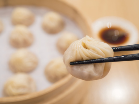 Closeup of Xiao Long Bao with chopsticks, Streamed Pork Dumplings Taiwan food (Selective Focus)