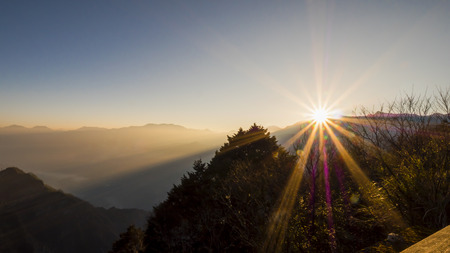 Sunrise over mountain with flare in the morning at Zhushan station, Alishan National Park, Taiwan. Stock Photo