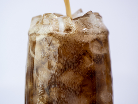 Selective fucus of pouring cola soft drink with ice in the glass on isolated  white background