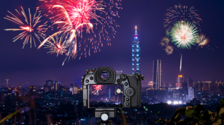 Digital camera over tripod on blur of firework with cityscape night light view of Taipei. Taiwan city skyline at twilight time Stock Photo