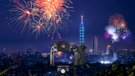 Digital camera over tripod on blur of firework with cityscape night light view of Taipei. Taiwan city skyline at twilight time 写真素材