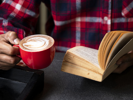Single man hold hot drink coffee cup of cappuccino and reading a book in the restaurant with his relax time.