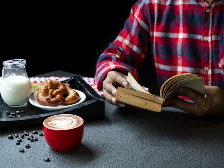 Single man seating to read a book in the restaurant with hot drink coffee cup of cappuccino and  bread with his relax time.