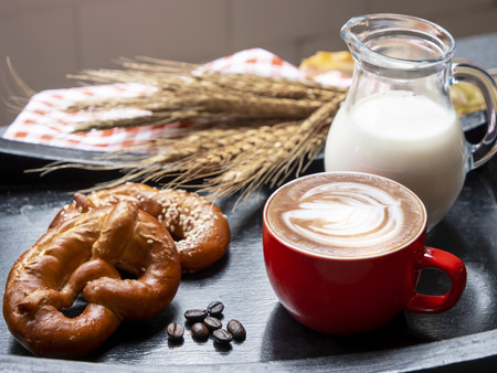 Hot drink coffee cup of cappuccino with beautiful foam, milk and bread on the table (Selective Focus) Stock Photo