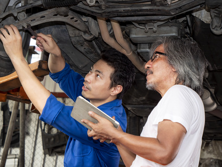 Two mechanic engineer repair the car and checklist fix item with tablet in the garage with sweat from hot weather