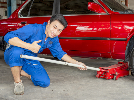 Young mechanic engineer smile, show excellent hand sign and use dirty red hydraulic floor jack to repair red car in the garage with sweat from hot weather Stock Photo