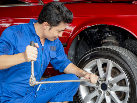 Young mechanic engineer use wheel wrench to change car tire in the garage with sweat from hot weather