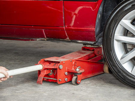 Mechanic engineer use dirty red hydraulic floor jack to repair red car in the garage