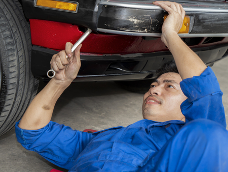 Mechanic engineer use wrench to repair the car in the garage with sweat from hot weather