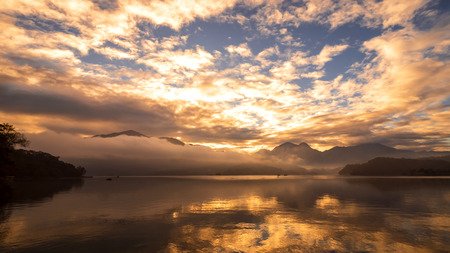 Reflection beautiful landscape of sunrise over the lake with fog in the morning at Sun Moon Lake, Nantou, Taiwan