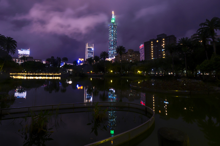 Cityscape night lignt view of Taipei. Taiwan city skyline with reflection from the lake at twilight time, public scene from the garden.