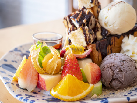 Close up of sweet dessert mix fruit honey toast with chocolate sauce and ice cream in the restaurant (Selective Focus)
