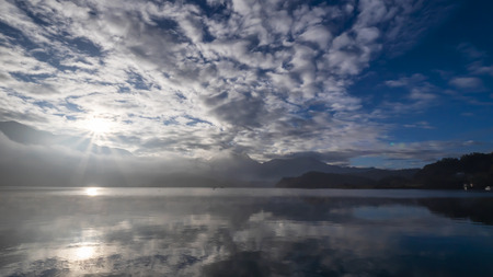 Reflection beautiful landscape of lake and mountain over blue sky and white cloud with fog in the morning at Sun Moon Lake, Nantou, Taiwan