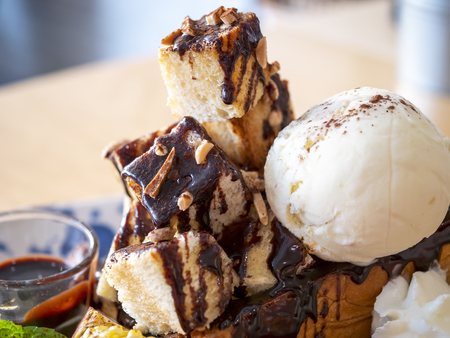 Close up of sweet dessert honey toast with chocolate sauce and ice cream in the restaurant (Selective Focus) Stock Photo