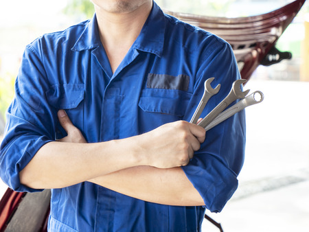 Mechanic engineer hold wrench on hand and standing in front of the car in the garage