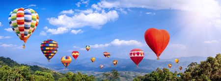 Panorama of colorful hot air balloon fly over mountain view with sunlight,  blue sky and white cloud at  Chiangrai, Thailand Stockfoto