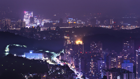 High view of cityscape night light view of Taipei with modern building and green mountain at the night. Green city in Taiwan