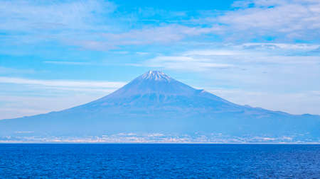 Fuji mountain landscape view over blue sky and white cloud from the ferry boat in the ocean at Suruga Bay, Shizuoka, Japan