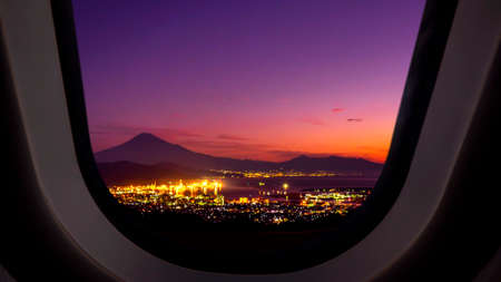 Airplane window view of sunrise over Fuji Mountain and Shimizu Industrial Port in Japan