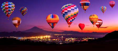 Panorama of sunrise over Fuji Mountain and Shimizu Industrial Port with colorful hot air balloon at Nihondaira, Shizuoka, Japan