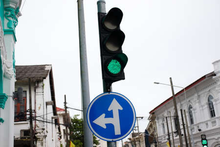 Green traffic light with traffic sign go straight and turn left. White sky. Phuket city, Thailand.