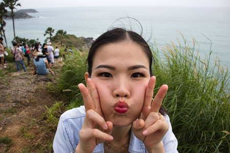 Woman pucker her lips posting to camera at Prom Thep cape , crowd in behind, the signature place of Phuket island : 18 October 2020 - Phuket island, Thailand.