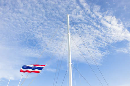 High angle view of mast rigging of yacht with blue cloudy sky, Thailand flag. Concept - adventure, fun active lifestyle, success.