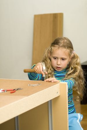 Girl helping to assemble new furniture