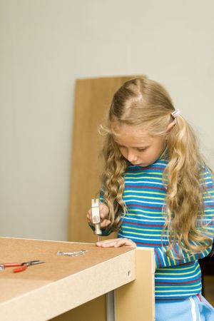 Girl helping to assemble new furniture photo