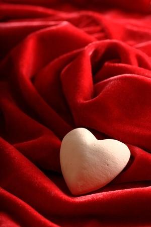 White stone heart on the red velvet fabric