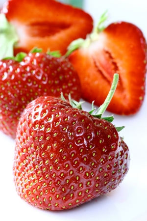 Strawberries on white background, one of them is sliced in half Stock Photo