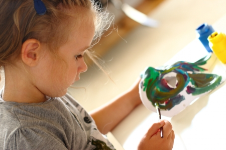 handicrafts: Little girl painting a carnival mask