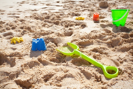 Sand toys, green bucket and a spade laying on a beach