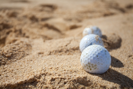 Three golf balls in a sand trap Stock Photo